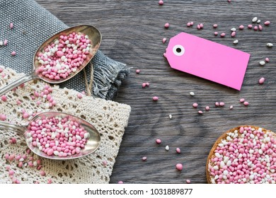 breakfast morning party scene with two vintage silver spoon with typical Dutch food muisjes, pink and white aniseed, for announcement birth of a daughter, baby girl