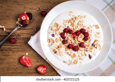 Breakfast of muesli and berries. Cranberry in heart shape. Top view, flat lay