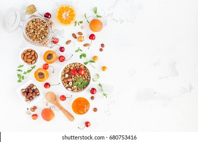 Breakfast with muesli, fruits, berries, nuts on white background. Healthy food concept. Flat lay, top view