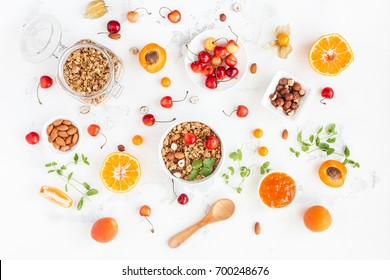 Breakfast with muesli, fruits, berries, nuts on white background. Healthy food concept. Flat lay, top view.