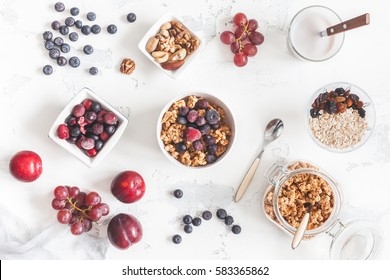 Breakfast with muesli, fruits, yogurt, frozen berries, nuts on white background. Healthy food concept. Flat lay, top view