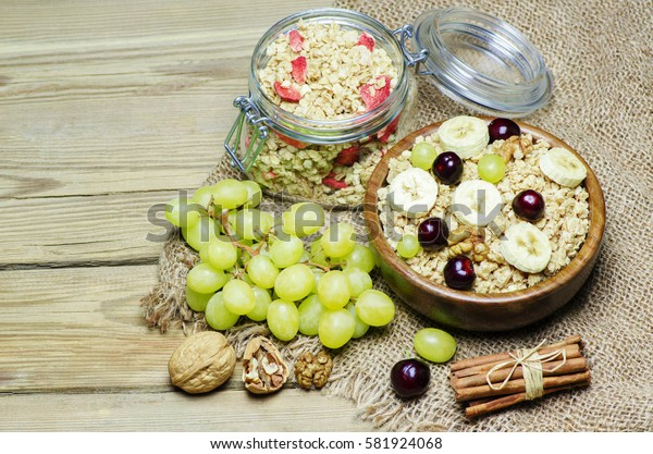 Breakfast with muesli and granola in wooden bowl placed with fresh fruits, cinnamon, nuts and jug of warm milk on wooden background.