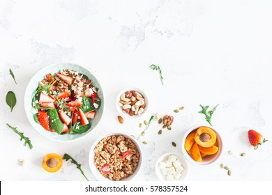 Breakfast with muesli, strawberry salad, fresh fruit, nuts on white background. Healthy food concept. Flat lay, top view.