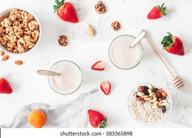 Breakfast with muesli, yogurt, strawberry, nuts on white background. Healthy food concept. Flat lay, top view