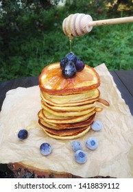 Breakfast in nature.  Pancakes with blueberries and honey