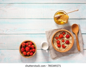 Breakfast with oat flakes, natural milk, fresh strawberry, almonds and honey on rustic background.