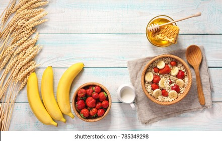 Breakfast with oat flakes and  natural milk, fresh banana, strawberry and honey on wooden table.Top view