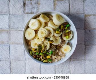 Breakfast: oatmeal with bananas, nuts, hemp seeds and hemp milk. Top view, toning.