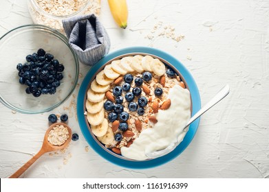 Breakfast, oatmeal with blueberry, banana almond and yogurt on a bowl in the morning.