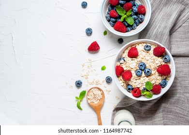 Breakfast, oatmeal with blueberry and raspberry on white bowl in the morning.