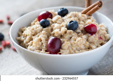 Breakfast oatmeal porridge with cinnamon, cranberries and blueberries, front view, selective focus