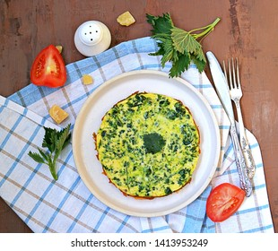 Breakfast, omelet with nettles on a white clay plate. Healthy food. Food from wild herbs. Top view, copy space. Italian food.