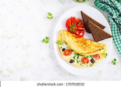 Breakfast. Omelette with tomatoes, black olives, cottage cheese and green herbs on white plate.  Frittata - italian omelet. Top view