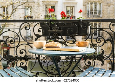 Breakfast on the balcony in Paris, France, in springtime with wrought iron railing and distant apartment buildings