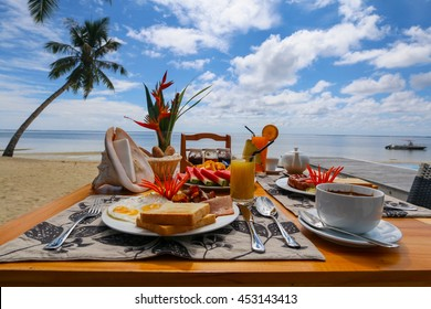 Breakfast on the beach with palm trees and blue sky in the background