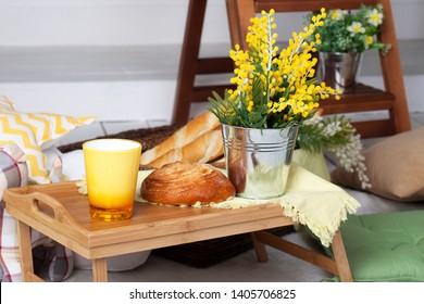 Breakfast on the cozy veranda. Homemade lemonade on the porch on a hot day. Summer country yard with pillows, mimosa flowers and lemonade. beautiful summer evening on wooden terrace or patio.