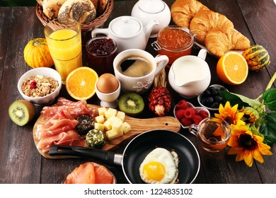 breakfast on table with bread buns, croissants, coffe and juice