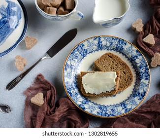 Breakfast on the table-top view. Rye bread with butter on a plate. Cane sugar. Beautiful Breakfast serving. Blue plates on grey background. Vintage Cutlery.  Brown runner.