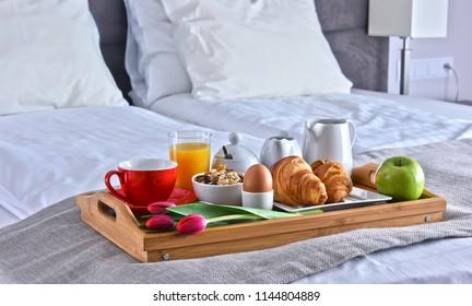 Breakfast on tray in bed in hotel room.