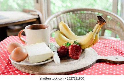 breakfast on the veranda, coffee, croissants. bananas, strawberries, eggs, butter; in the background a chair and greens