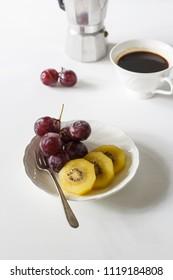 breakfast on white table, grape, kiwi and espresso coffee.