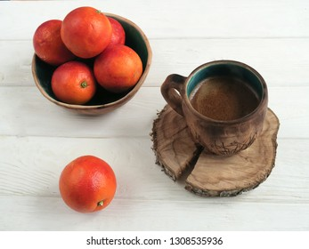 Breakfast on a white wooden table with a bowl of red oranges and a mug of black coffee