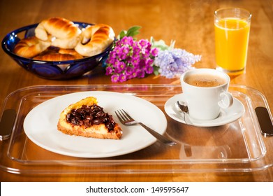 Breakfast on wooden table, with cherry cake, coffee with milk, croissants and orange juice on a tray.