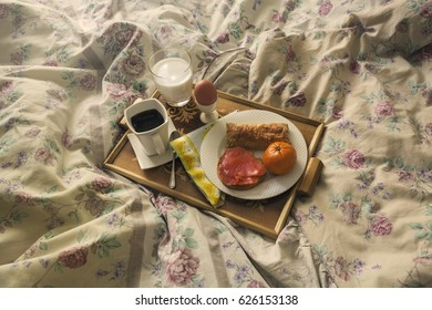 Breakfast on a wooden tray on a bed with coffee, milk, salmon, an orange, an egg and milk