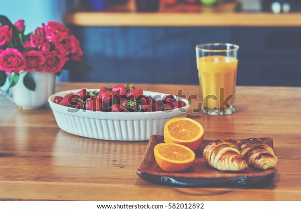Breakfast of orange juice, croissant and strawberry.