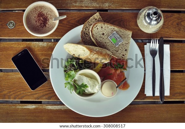 Breakfast from organic ingredients including wild salmon, brown bread, boiled egg, fresh cheesae and green salad, accompanied with hot chocolate, and a smart phone.