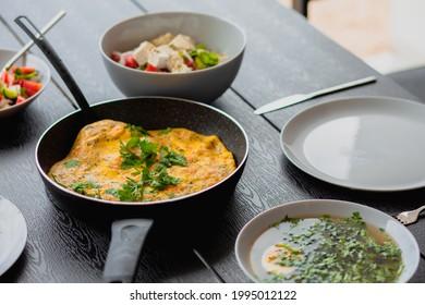 Breakfast outside. Shrimp omelet for breakfast. Omelet in a frying pan for breakfast. Lunch for a man. Fried omelet with vegetables. Summer food on the street. Egg soup. Regular food. Diet. Bouillon