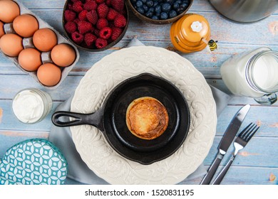 breakfast, A pancake on an iron cast skillet on rustic wood table with organic eggs, sour cream, honey, milk, raspberry, blueberry, almonds, pecans