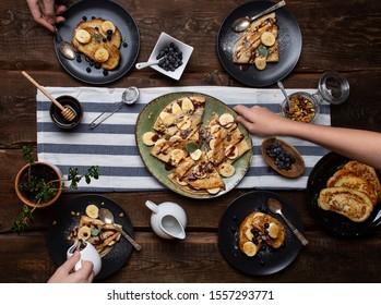 Frühstück mit Pfannkuchen mit Bananensoße, Schokoladennuss-Soße und süßen Croutons