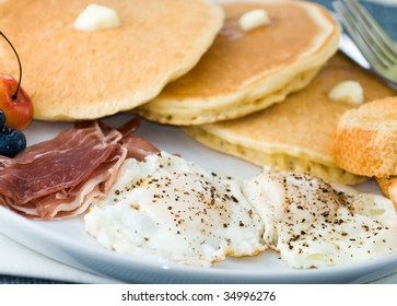 Breakfast of pancakes, eggs, ham, toast and fruit with lemonade and coffee