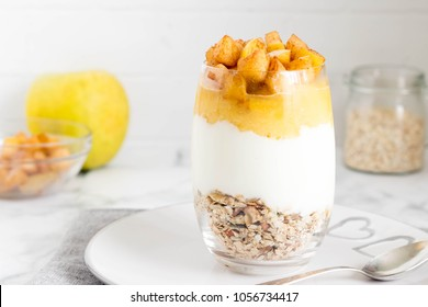 Breakfast parfait in a glass with crunchy nuts and oats, yogurt, apple puree and fresh fruit served on kitchen table.