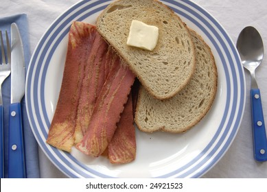 Breakfast plate of bread and butter and soy bacon.