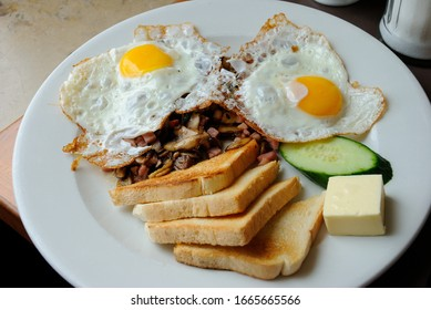 Breakfast plate with fried eggs, mushrooms, cucumber, butter and toasted white bread in Munich, Germany