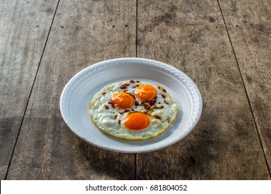 Breakfast plate, with fried eggs on the wood floor.