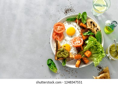Breakfast plate with fried eggs, vegetables, mushrooms and toast on gray concrete background copy space. Top view. Breakfast table. Healthy breakfast table concept