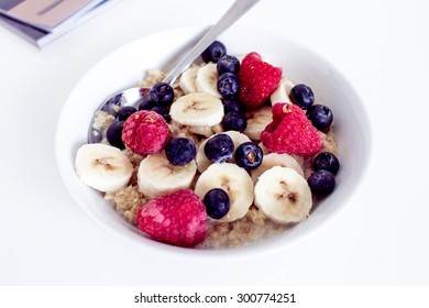 Breakfast of porridge, banana and berries including blueberries and raspberries