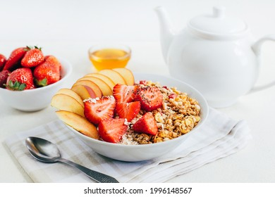 breakfast porridge oatmeal with cereal granola strawberries peaches honey in a white plate on the background of a white teapot and bowls with honey on a white plate