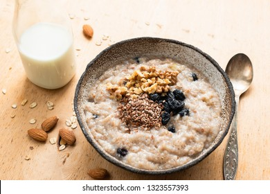 Breakfast porridge oats in bowl on wooden table. Oatmeal porridge with raisins, nuts and linseeds prepared with almond milk