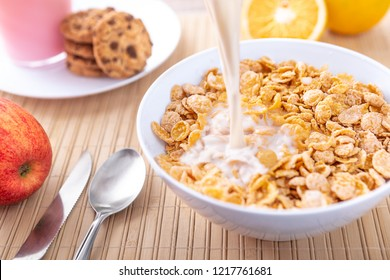 Breakfast pouring milk into corn flakes creating splash apple and orange fruit cookies