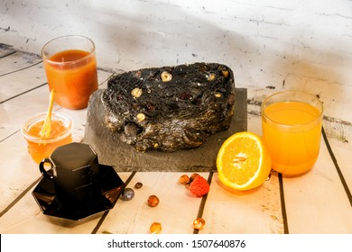 Breakfast preparation with coffee a tomato juice and a fresh orange juice honey fresh seasonal fruit and a black bread with charcoal cereals and dried fruits artisanal