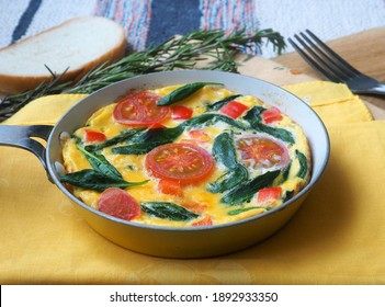Breakfast is prepared on the table: an omelet with tomatoes and spinach, a slice of bread and a fork. A frying pan with an omelet stands on a yellow napkin and a wooden board