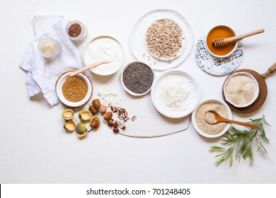 Breakfast raw ingredients group with yogurt bowl almonds flax seeds oat chia seeds honey couscous quinoa coconut flakes linen jelly diet supplement grain cereal overhead