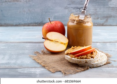 Breakfast with rice cakes, peanut butter and apple on old wooden background