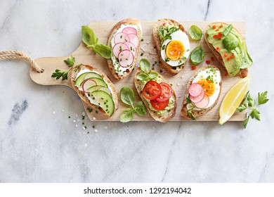 Breakfast sandwich bread with avocado, egg, radishes and tomatoes. Bruschetta or healthy snack ideas