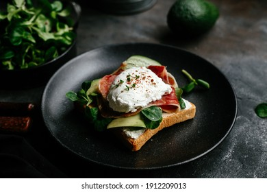 Breakfast. Sandwich with ham, poached egg, avocado and spinach in a plate on a dark background