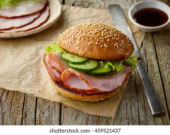 breakfast sandwich with smoked meat on wooden table